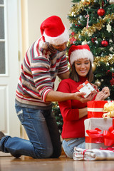 Romantic young man surprised his beautiful girlfriend with Christmas present while she is decorating Christmas tree at home.