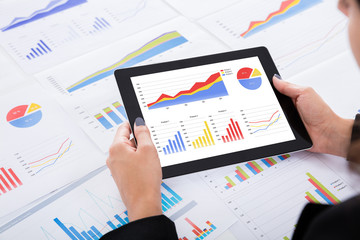 Businesswoman Analyzing Financial Graphs Using Digital Tablet