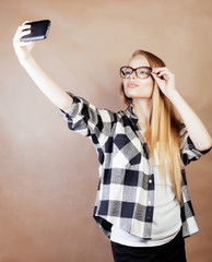 young pretty blond hipster girl making selfie on warm brown background, lifestyle people concept