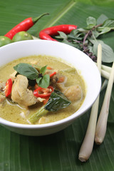Thai green curry chicken on banana leaf surface