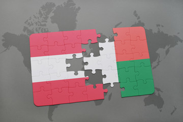 puzzle with the national flag of austria and madagascar on a world map background.