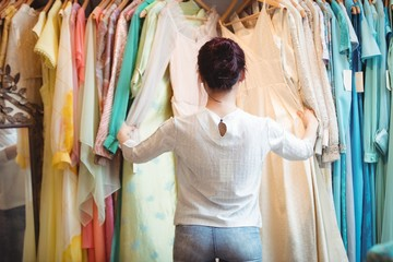 Woman selecting a clothes from hanger