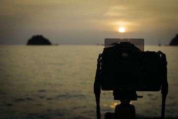 silhouette image of digital camera on tripod during sunset.sea and island background