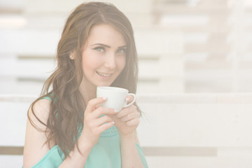 Young beautiful woman holds cup of tea in cafe.