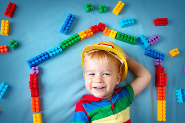 boy lying on the blanket with blocks in house shape