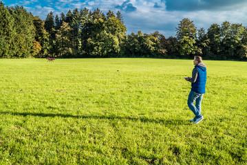 Mann auf Wiese nahe Waldstück lenkt seine Drohne