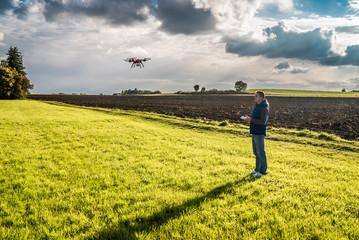 Mann lenkt Drohnenflug im Sonnenuntergang