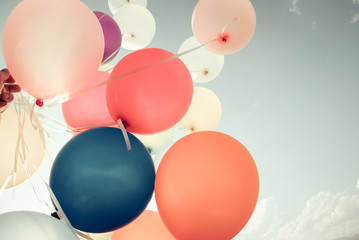Wall Mural - Colorful balloons flying on sky with a retro vintage filter effect. The concept of happy birthday in summer and wedding honeymoon party - usage for background (vintage color tone)