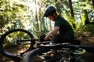 Male cyclist repairing his bicycle in forest