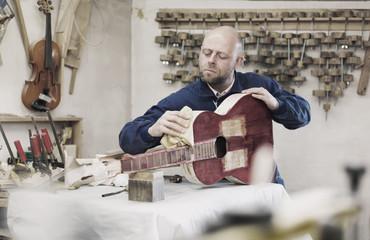 Carpenter preparing guitar for varnishing