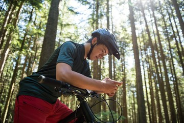 Male cyclist using mobile phone in forest