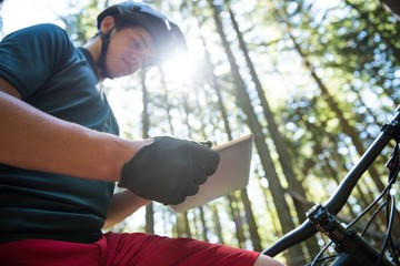 Male cyclist using digital tablet in forest