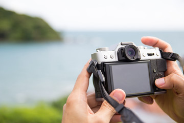 Hand holding a mirrorless digital camera prepare for take a land