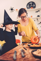 Daughter and mother creating Jack-O-Lantern