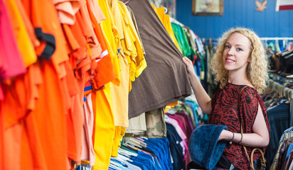 Woman shopping for t-shirts in a thrift store