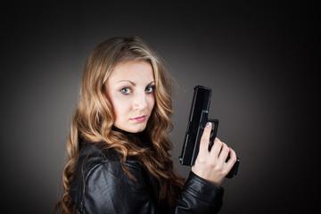Top secret FBI female agent holding pistol (very harsh light for underline the atmosphere)