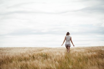 Rear view of woman walking through wheat field