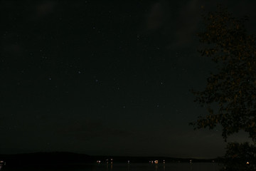 long exposure stars trees lake and sky