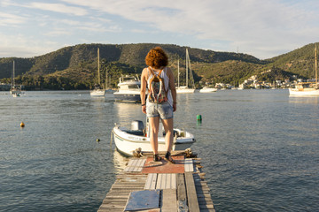 A woman on a wooden platform in Greece staring at the sea