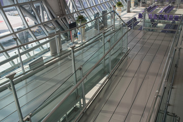 Airport terminal interior with rows of empty seats, city view an