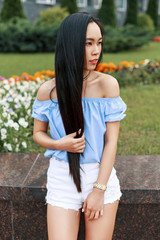 Beautiful young asian woman in a stylish blue blouse posing near the summer restaurant