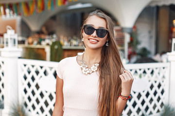 Portrait of beautiful cheerful girl in sunglasses near white vintage wooden fence