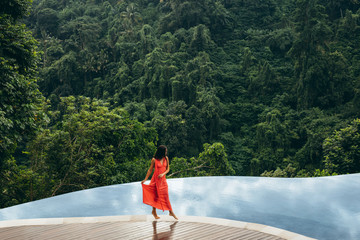 Beautiful woman walking on edge of infinity pool