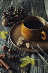 Autumn mood: cup of coffee, nuts and autumn leaves