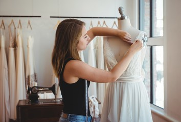 Female fashion designer adjusting the dress on mannequin