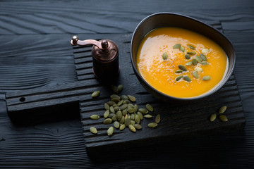 Bowl with pumpkin cream-soup on a black wooden serving board