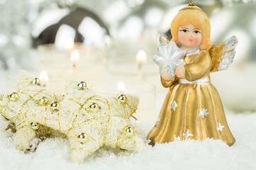 Angel Figurine and Gold Stars on Snow with Candles