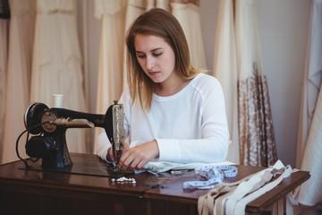 Female dressmaker sewing in the studio