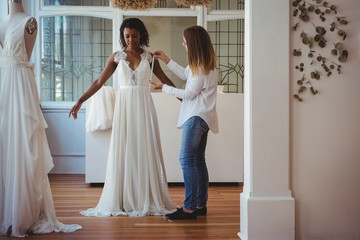 Female fashion designer taking measure of woman