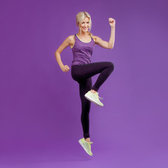 Beautiful young girl in a pose runner. Studio background, purple