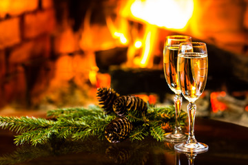 Two glasses of wine and Christmas New Year decoration, fireplace