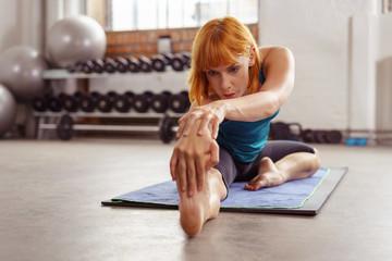 sportliche frau im fitness-studio dehnt ihre beinmuskulatur