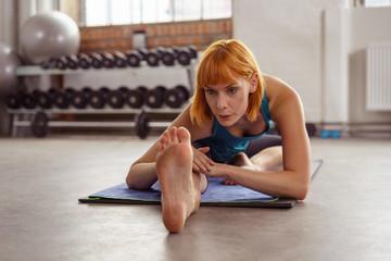 frau dehnt ihre beine im fitness-center
