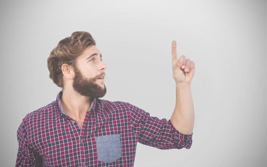 Composite image of hipster pointing upwards