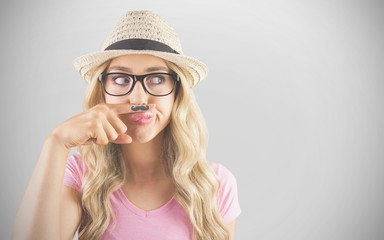 Composite image of a beautiful hipster having a fake mustache