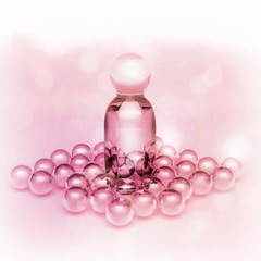 Perfume oil in a glass bottles and pearl beads on pink.