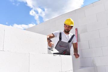 Neubau weines Hauses: Bauarbeiter mauert den Rohbau