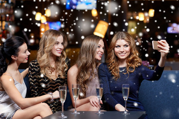 women with champagne taking selfie at night club