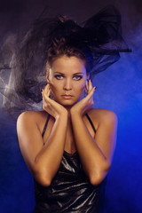 Fashion Art Portrait Of Beautiful Girl over blue lights & smoke. Closeup portrait of model posing at studio.