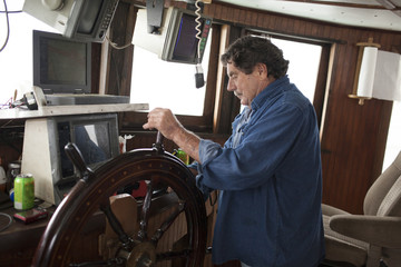 Commercial fishing boat captain at the wheel