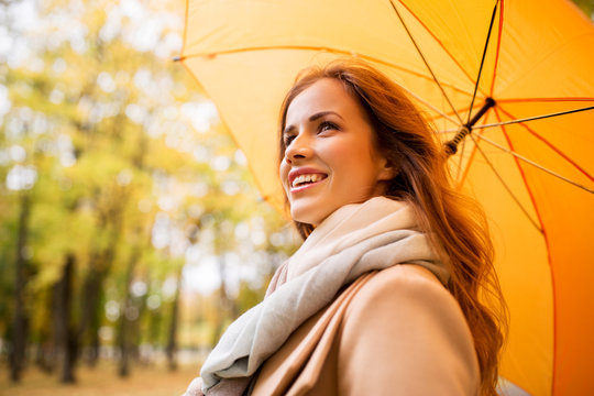 happy woman with umbrella walking in autumn park