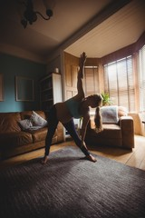 Pregnant woman performing stretching exercise in living room