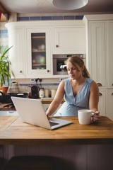 Pregnant woman using laptop while having coffee in kitchen