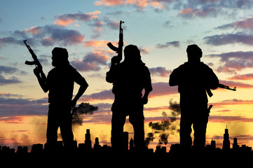 Terrorist concept. Silhouette terrorists, against the background of the urban landscape in smoke