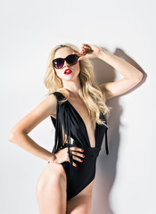 Studio fashion shot: sexy young girl wearing swimsuit and glasses