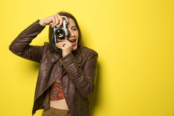 Fashion young girl makes the photo with old camera. Yellow backg